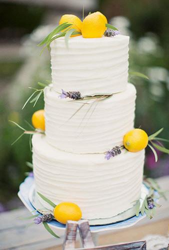 λευκή γαμήλια τούρτα με την προσθήκη μερικών λεμονιών