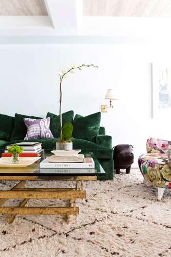 Σκούρος πράσινος καναπές σε καθιστικό.
