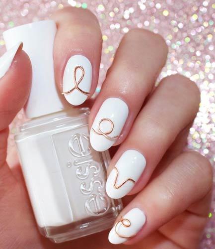 Λευκά νύχια με χρυσά γράμματα.