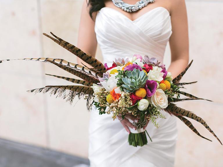 Νυφική ανθοδέσμη με φωτεινά άνθη και φτερά.